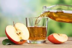Succo di mele che versa dalle mele rosse in un vetro Fotografia Stock