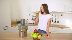 Succo di mele - mele juicing della donna e berlo fresco a casa in cucina Macchina del succo e cibo sano felici video d archivio