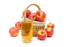 Succo di mele in un vetro e un canestro delle mele su un backgro bianco Fotografia Stock Libera da Diritti