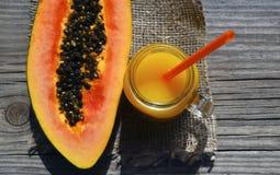 Succo di papaia di recente urgente in un barattolo di vetro ed in una frutta divisa in due matura della papaia sulla vecchia tavo Fotografia Stock