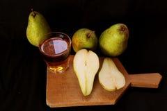 Succo di pera casalingo fresco con una certa frutta fresca Pere saporite succose del raccolto di autunno della pera su fondo nero fotografie stock