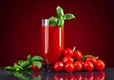 Succo di pomodoro con i pomodori e basilico verde sulla tavola nera immagine stock