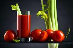 Succo di pomodoro con i pomodori ed i bastoni di sedano Immagine Stock