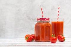 Succo di pomodoro fresco in vetri e pomodori ciliegia su fondo leggero Con lo spazio della copia fotografia stock