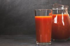 Succo di pomodoro fresco in vetro sulla tavola scura fotografie stock libere da diritti