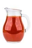 Succo di pomodoro in lanciatore di vetro trasparente isolato su bianco fotografie stock