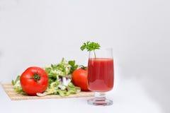 Succo di pomodoro in un vetro con i pomodori ed i verdi Immagini Stock Libere da Diritti