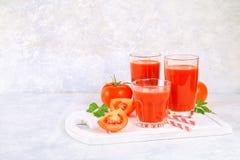 Succo di pomodoro in vetri su una tavola concreta grigia immagini stock