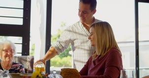 Succo di versamento dell'uomo felice in vetro sul tavolo da pranzo 4k archivi video