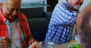 Succo di versamento della donna senior in vetro al suo amico 4k stock footage