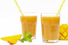 Succo fresco del mango del frullato della frutta tropicale e mango fresco su un fondo bianco fotografia stock libera da diritti