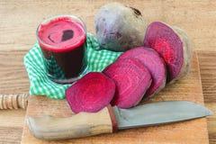 Succo fresco della barbabietola in vetro e barbabietola affettata sul bordo di legno con il coltello ed il tovagliolo Fotografia Stock