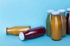 Succo fresco di Differenr in bottiglie su fondo blu Concetto sano immagini stock libere da diritti