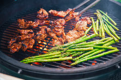 Succulent κομμάτι του μαγειρέματος κρέατος σε μια σχάρα με μια πλευρά του σπαραγγιού Να δειπνήσει έννοια της διατροφής _ Τρόφιμα Στοκ Εικόνα