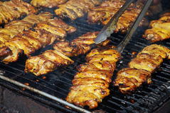 Succulent Chicken. Chef turning chicken on the grill Royalty Free Stock Photo