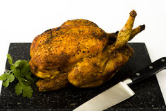 Roast chicken and coriander on chopping board. Succulent and delicious looking roast chicken on a black marble chopping board with coriander Stock Photography