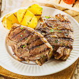 Succulent grilled barbecued lamb chops. Close up of a serving of two succulent grilled barbecued lamb chops seasoned with fresh herbs served with potatoes at a stock images