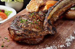 Succulent grilled tomahawk beef steak. On the bone with vegetables on cutting board stock photo