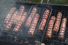 Succulent meat fried sausages fried on the grill on the embers. Bbq, meat, beef, food cooking royalty free stock image
