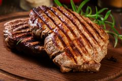 Succulent portions of grilled fillet mignon served with rosemary. On an wooden board stock photography