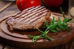 Succulent portions of grilled fillet mignon served with rosemary. On an wooden board royalty free stock photo