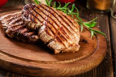 Succulent portions of grilled fillet mignon served with rosemary. On an wooden board royalty free stock image