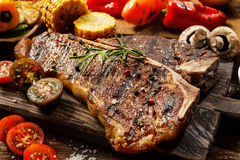 Succulent tender grilled porterhouse steak. Close up of a succulent tender grilled porterhouse steak seasoned with pepper and rosemary on a wooden board with royalty free stock photo