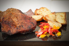 Succulent thick juicy portions of grilled fillet steak served with roasted potatoes and peppers on black granite board Stock Image