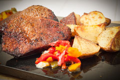 Succulent thick juicy portions of grilled fillet steak served with roasted potatoes and peppers on black granite board Stock Photography