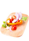 Succulent vegetables and cheese on chopping board. Paprika, tomatoes, lettuce, red onion and cheese on a kitchen board Stock Photos
