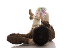 Sucess. A sucesseful business man lying on the floor looking to euros banknotes Royalty Free Stock Image