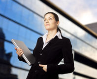 Sucessful Businesswoman. Businesswoman holds a modern laptop in front of an office building Royalty Free Stock Images