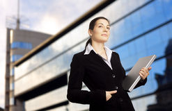 Sucessful Businesswoman. Businesswoman holds a modern laptop in front of an office building Stock Photography