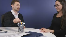 Sucessful deal between businessman and businesswoman. Two business people sits in the office at the table and discussing the work issues. Executive director stock footage