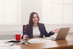 Business woman working on laptop at office. Sucessful project. Happy business woman sitting at table in office and point at laptop, enjoying new achievement Stock Photography