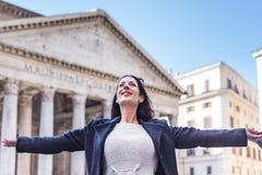 Sucessfuls y las mujeres felices abren los brazos y la sonrisa que miran en el cielo Imagenes de archivo