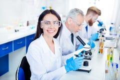 Sucesso em inventar a nova tecnologia! O técnico de laboratório novo está sorrindo fotografia de stock