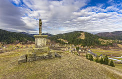 Sucevita. The cross on top of the hill behind Sucevita Monastery and the monastery and village in the backdrop Royalty Free Stock Images