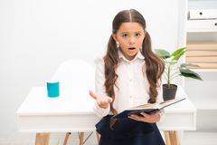 Such difficult topic. Studying difficulties. Girl read book while stand table white interior. Schoolgirl studying. Textbook. Kid school uniform confused face royalty free stock photos