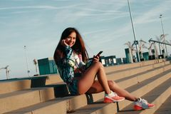Such a great song!. Attractive young woman in sports clothing looking at camera and smiling while sitting on the steps outdoors royalty free stock image