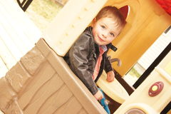 Such a ham. Little boy sitting in a playhouse hamming it up for the camera Stock Image