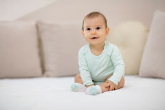 Such a happy little baby girl. Beautiful cute soft baby girl sitting on bed Stock Images