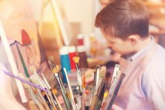 Side view on teenage boy in painting class royalty free stock photography