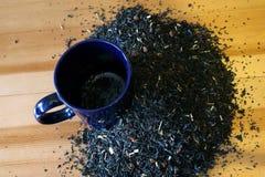 Sucha herbata i błękitny kubek rozpraszają na drewnianym stole fotografia stock