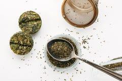 Sucha zielona herbata w metal łyżce z ściśnięty herbacianym blisko na białym tle, odgórny widok zdjęcia royalty free