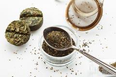 Sucha zielona herbata w metal łyżce z ściśnięty herbacianym blisko na białym tle, odgórny widok, zbliżenie strzał fotografia royalty free