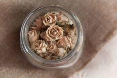 Suche róże dla zdroju w szklanym pucharze Pączki suche róże w szklanej butelce na jutowym tle Zdjęcia Stock