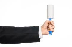 Suchego cleaning i biznesu temat: mężczyzna trzyma błękitnego kleistego muśnięcie odzieżowy i meblarski dla czyścić od pyłu w cza Obrazy Royalty Free