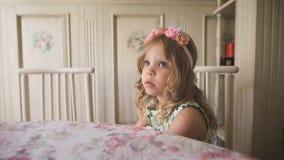 Suchen nach Inspiration Durchdachtes kleines Mädchen, das beim Sitzen dem Tisch in einem hellen Raum weg betrachtet stock footage