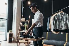 Suchen nach neuen Ideen Ernster junger Mann, der Männerkleidung vereinbart Stockfotos